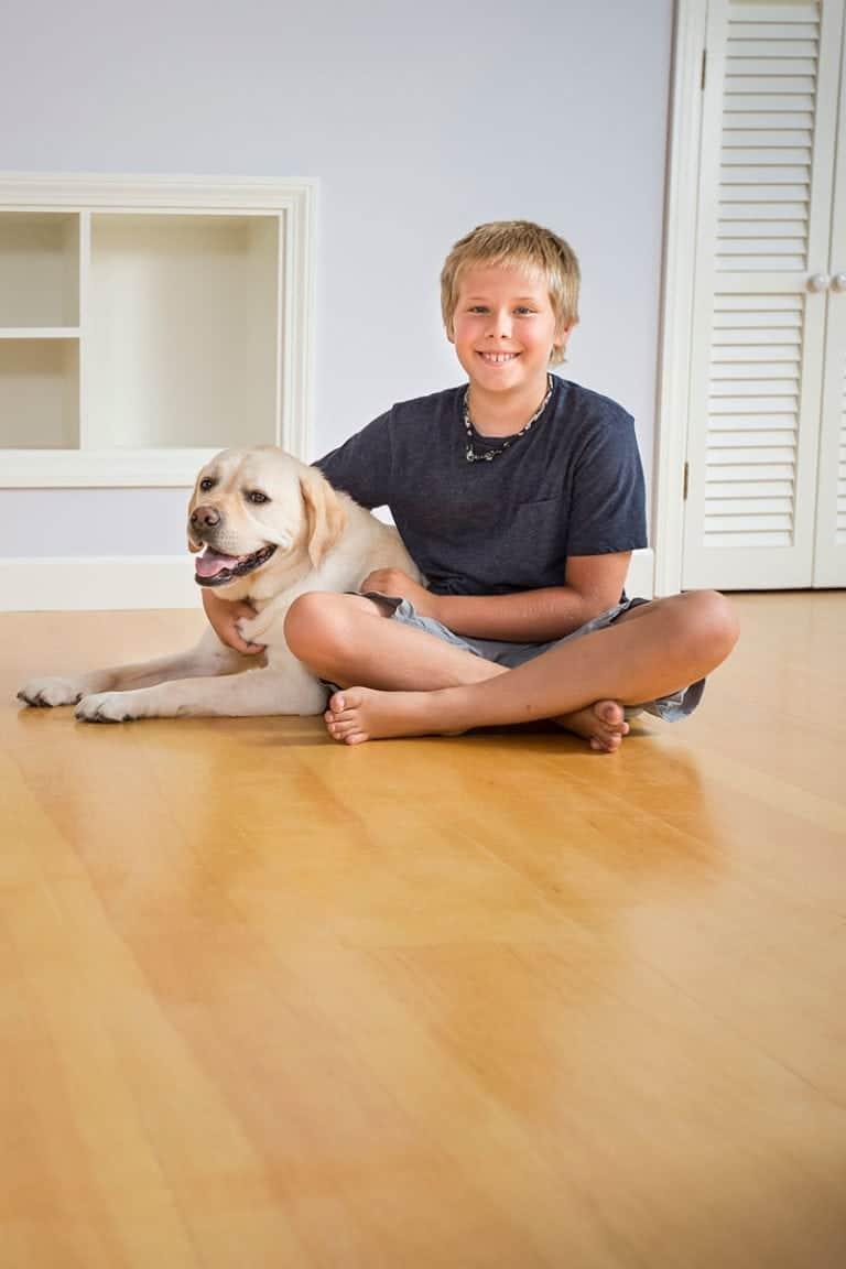 Boy and dog sitting on white pine flooring