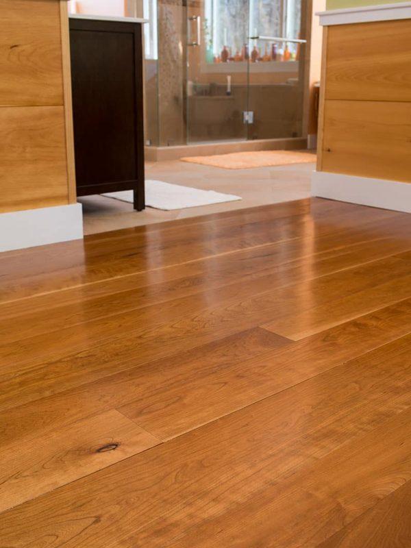 cherry wide plank flooring installed in bathroom