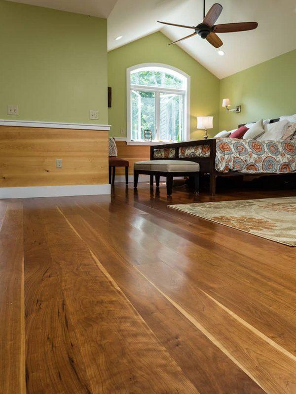 cherry wide plank flooring installed in bedroom